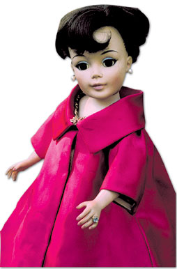 "This 21-inch ""Jacqueline Kennedy"" portrait doll from the 1960s is dressed in a copy of the First Lady's inaugural ball gown and cloak. Notice her ring and the tag (far right)."