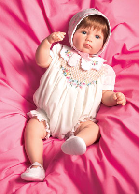 """""""Simple Treasures"""" wears apparel designed by Martha Pullen. Her attire consists of a soft cotton romper, and features hand smocking trimmed with embroidery. Part of the Yesteryear Treasures series, the doll is attractively priced at $185."""
