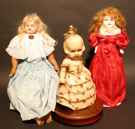 An early wax doll flanked by two porcelain dolls