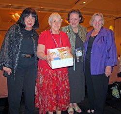 From left: Alexander Doll Company President Gale Jarvis makes a special presentation to club founder Margaret Winson (second from the left) as Convention Chairwoman Marsha Hunter and MADC President Carol Dowdy look on.