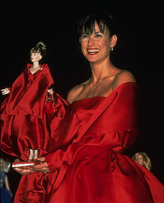 Moore holds her lookalike doll aloft at the AmFar Auction. Courtesy of DOLLS magazine archive