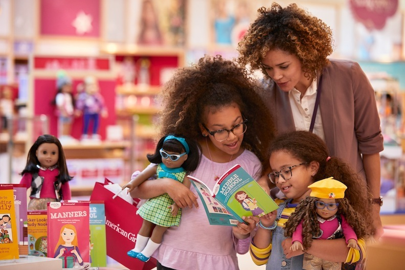 American Girl has always encouraged families to learn together. Here, a mom and her daughters visit one of the retail locations and review a fun, educational book. Fingers crossed, retail will reopen in the near future!