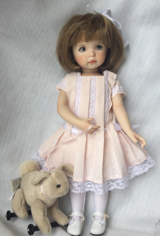 """""""Little Lou is one of my favorites,"""" Norton said. """"She is 10 inches and has such endearing features, with deep periwinkle eyes. Her dress is made from warm pink dotted Swiss and is trimmed with cotton heirloom lace. She comes with her bunny pull toy."""""""