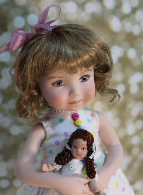 Bailey is a 10.5-inch full porcelain doll made from a Dianna Effner mold. Her polka-dot dress is adorned with lace and colorful tiny buttons. She holds a miniature porcelain doll dressed in matching material.