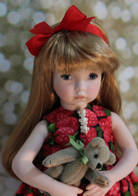 Blake, from Dianna Effner's Emily face sculpt, wears a dress adorned with with lace and Swarovski pearl accents. She holds a miniature cashmere teddy bear.