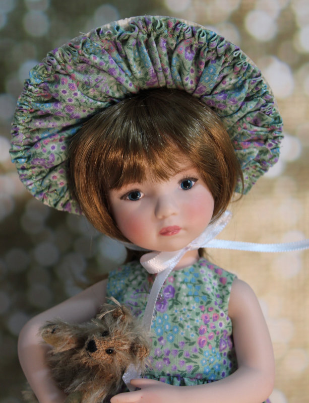 Dayna wears a hand-embellished Victorian poke bonnet and holds her favorite mohair teddy bear. She was created from a Dianna Effner Little Darling doll mold and has hand-painted blue eyes.