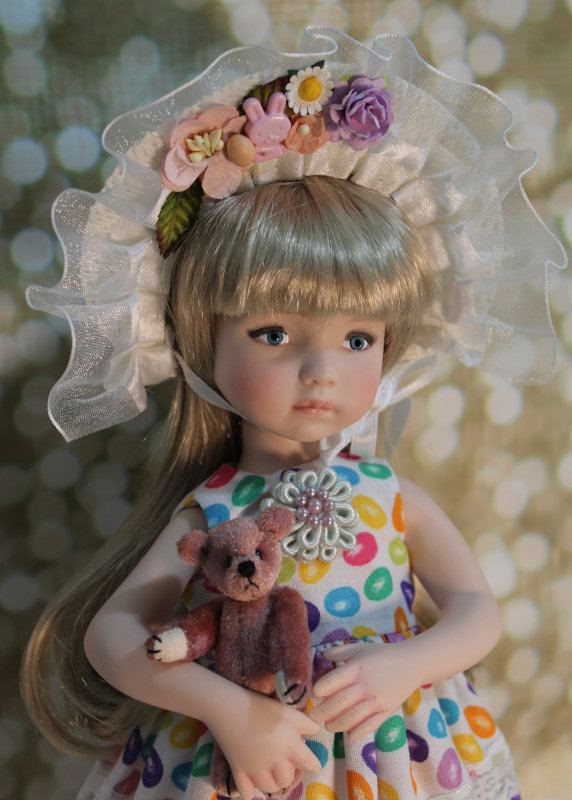 Iris, a Little Darling #1 face sculpt, is dressed in her Easter finest in a colorful jelly bean print dress adorned with lace and an embellished Easter bonnet.