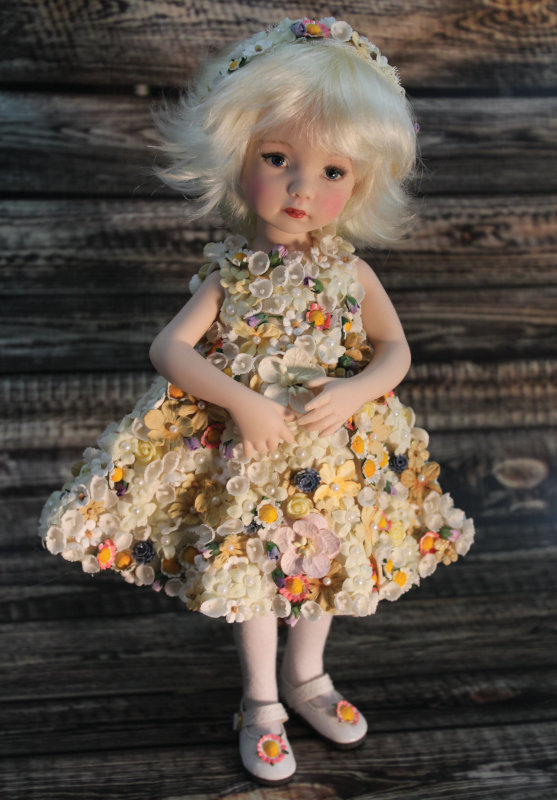 Les Fleurs du Printemps (The Flowers of Spring), 10.5 inches, is a full porcelain doll made from a Dianna Effner mold. Her knee-length sleeveless dress incorporates vintage millinary lily-of-the-valley cotton flowers, a variety of paper flowers including cherry blossoms handmade from mulberry paper, and tiny silk flowers. Over 200 Swarovski pearls have been hand-applied to silk flowers on her dress.