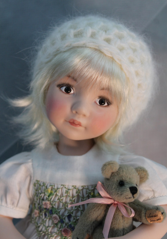 Melissa wears a hand-crocheted hat made from French Angora yarn and holds her favorite teddy bear. She was created from a Dianna Effner Wednesday's Child doll mold and has hand-painted brown eyes.