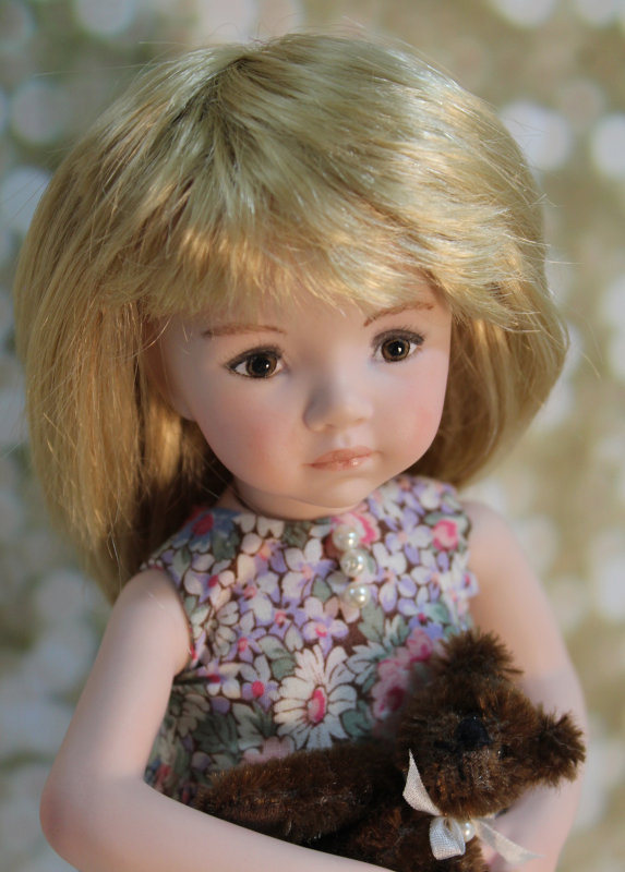Sawyer is a 10.5-inch full porcelain doll hand-crafted from a Dianna Effner April doll mold with hand-painted brown eyes. Her floral-print dress has heirloom lace on the skirt and delicate Swarovski pearls sewn on the bodice.