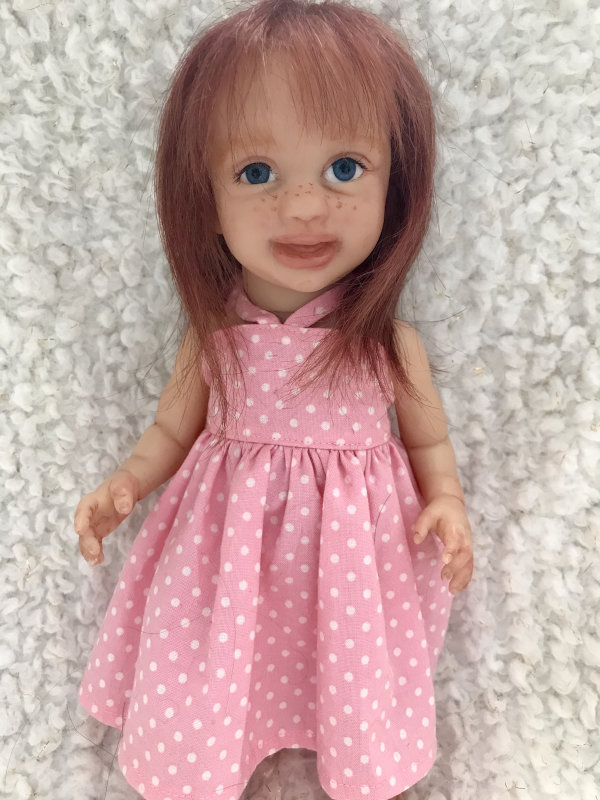 Fawn is an 11-inch soft-vinyl reborn from Marita Winters' Annika edition. Brooks used glass eyes, mohair, and Genesis paints to finish the doll. Her polka-dot dress is by Grannysstitchen.