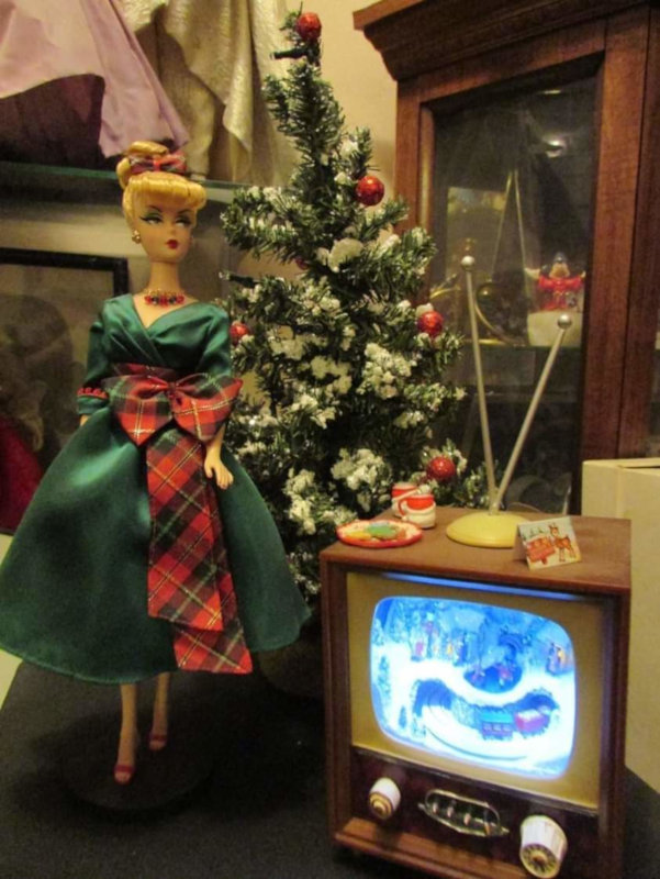 "Donna Bell: ""My Barbie is watching a Xmas special for the holidays, with her cocoa and cookies (and a greeting card from Ken). The little TV is actually a music box — a little train revolves around inside it. Cool gift from years ago."""