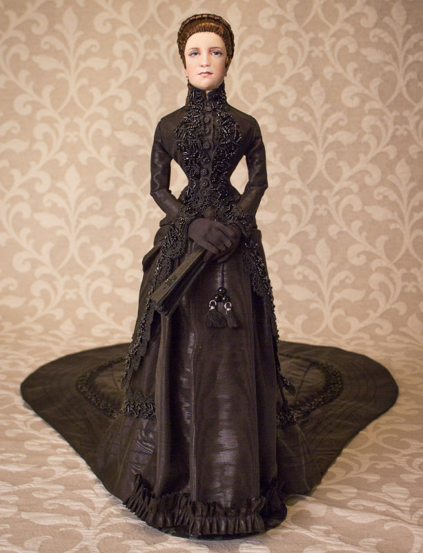 Empress Elizabeth of Austria lived from 1837 to 1898. Wray's 24-inch OOAK cloth depiction is jointed at the shoulders, upper arms, hands, wrists, hips, knees, and ankles. She wears authentic silk underclothes, undershirt, and breeches, a functional corset, bustle, and petticoat. Her jacket skirt is made from black watermarked fabric trimmed in black lace and heavily hand-beaded trim. She wears low-heeled slippers with beaded bows and carries a handmade hand fan.