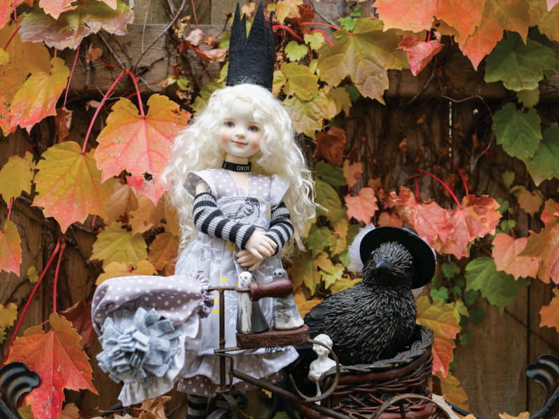 """Jennie MacDonald: """"Created by April Norton from Dianne Effner's Little Darling Mold #3, Nina first appeared in Norton's Everything's in Black and White collection (as seen in DOLLS' June/July 2016 issue). I've loved dressing her in Chris Miller's meticulously designed and crafted ensembles. Her crown is from a Haute Doll-featured outfit. Lenore the raven wears Nina's original party hat. Ghosts by The York Ghost Merchants."""""""