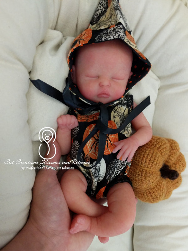 """Cat Johnson: """"Silicone mini baby sculpted by Jennifer Costello-DelCegno and painted by me, in her Halloween outfit and crochet pumpkin by me as well."""""""