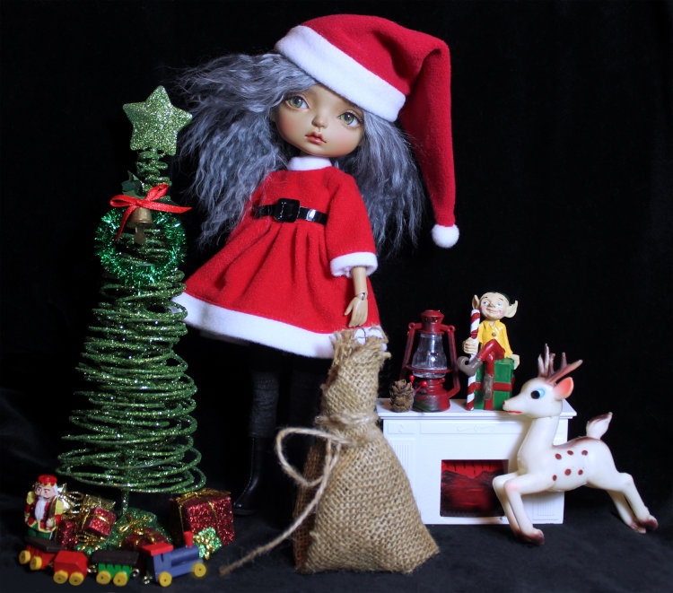"Nadine Bandler: ""MaskCat Gladys in a Santa outfit with assorted dollhouse miniatures."""