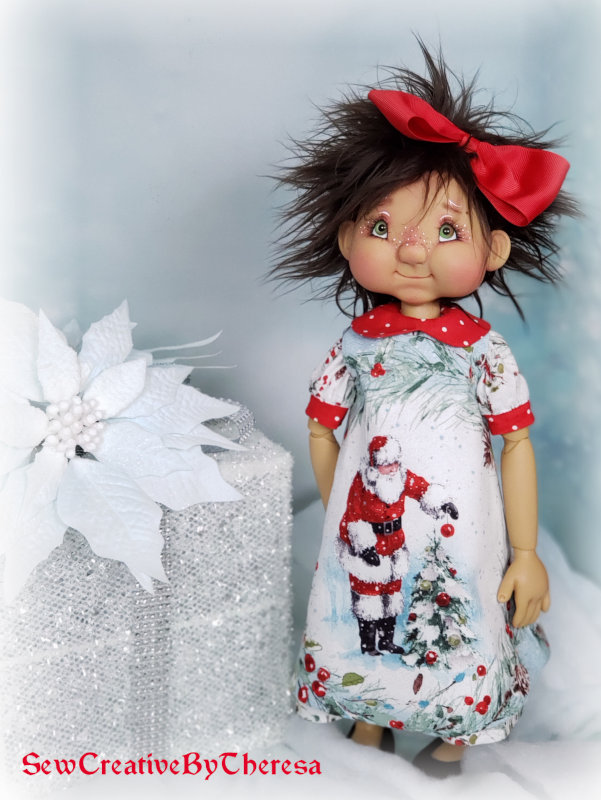 "Theresa Wagner: ""Kimmy Arnold's Franny is ready for Christmas in this dress and pinafore set. The front displays a beautiful picture of Santa outside."""