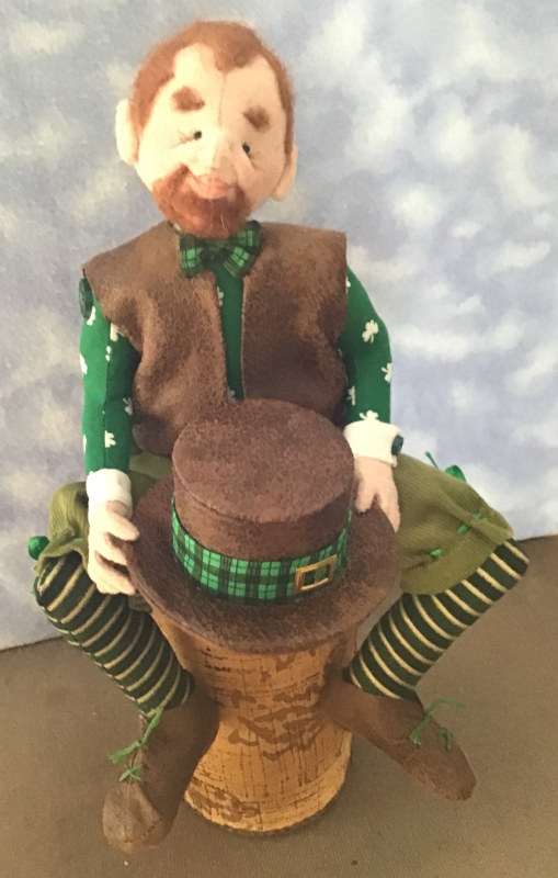 """Joan Paul: """"Sheamus is a St. Patrick's Day leprechaun. He is a cloth doll. I made his vest, hat, and shoes from fine leather. His red hair and beard are wool."""""""