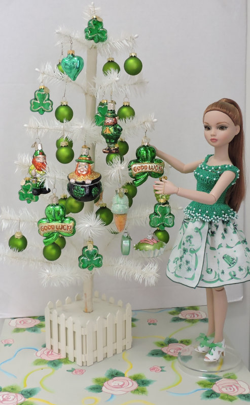 """Sandy Halstead: """"My lovely red-haired Ellowyne Wilde doll is putting the ornaments on her special St. Patrick's Day tree in an outfit I made for her consisting of a crocheted top decorated with beads and a skirt made of a vintage hankie in a St. Patrick's Day print!"""""""