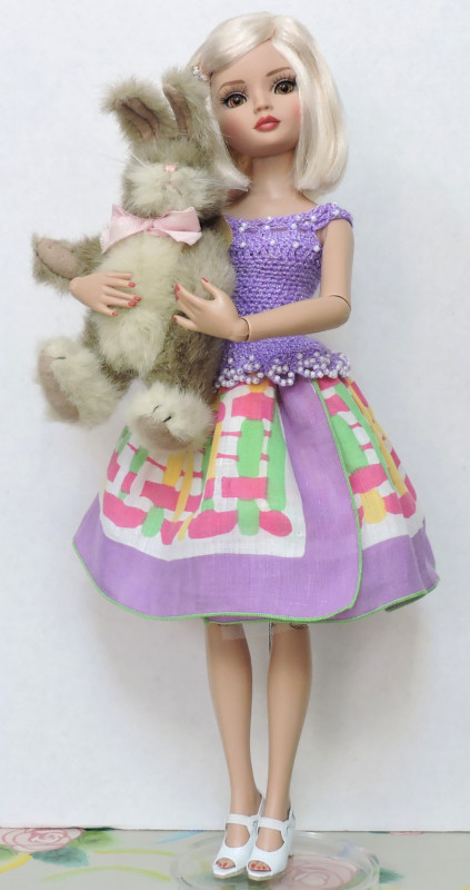 "Sandy Halstead: ""My Ellowyne Wilde Doll is looking forward to beautiful spring days and Easter with Alice, her cuddly bunny! I made her outfit — a beaded crochet top and vintage hankie skirt — for her to celebrate the season!"""