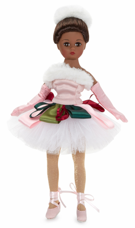 Jolly Jete is a 10-inch Cissette in a ballet ensemble for a holiday dance performance. Her satin dress with tutu has colorful ribbon trim and white faux fur accents, along with nude tights, satin ballet shoes with ribbon ties, long satin gloves, and a faux fur hat. The doll is offered in dark skin tone with brown eyes and brunette hair or in light skin tone with blue eyes and brunette hair.
