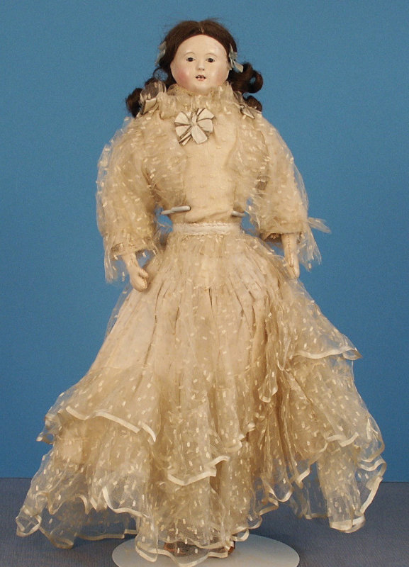 A 16-inch French papier-mâché shoulder head doll with original wig featuring center part and long tight curls, dark glass inset eyes, bamboo teeth, and original clothing. Photo courtesy of Foulke Archives
