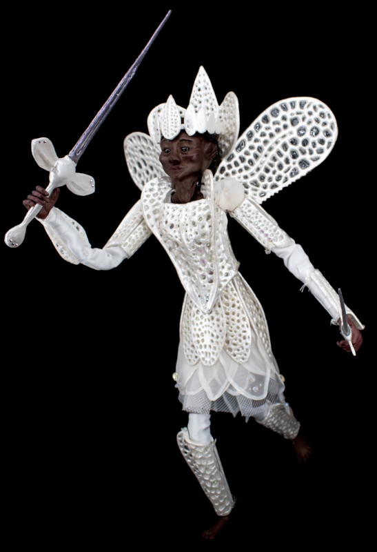 Dove, 18 inches, is a brave defender of peace. She wears 3D printed armor inspired by the delicate, iridescent pattern of lace bugs (tingidae). Her face, hands and feet are sculpted in polymer clay with wool locks and glass eyes. Under her armor, she wears silk, leather, and an organza skirt adorned with glass beads.