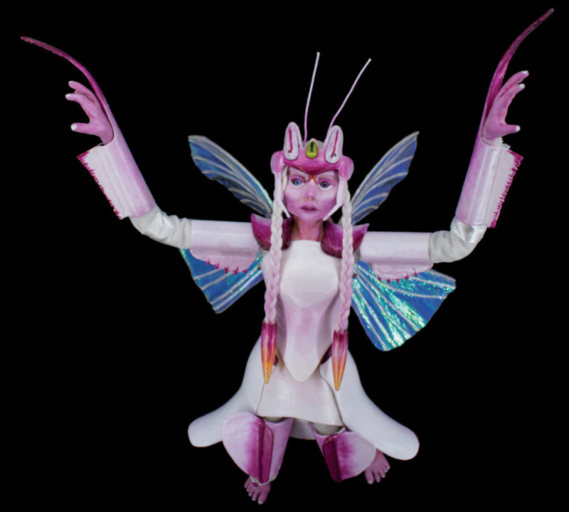 Elanora, 19 inches, is inspired by the orchid mantis (hymenoptera coronatus). Elanora has a polymer-clay head, hands, and feet with glass eyes and wool hair. Her armor is 3D printed and her wings are made of cellophane decorated with crystals.